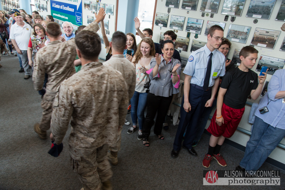 Students high-five the soldiers as they enter the terminal