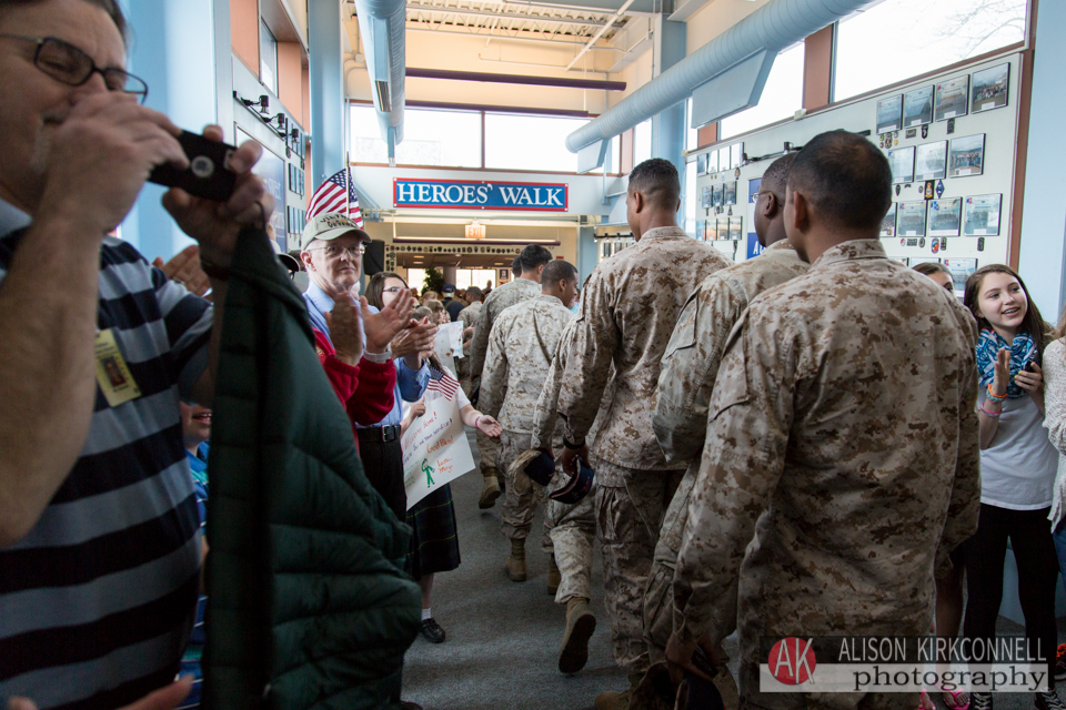 "The terminal entrance is called ""Heroes' Walk"". Greeters line the way, giving thanks for the soldiers' service and offering handshakes and hugs. Mr. Boisvert is on the left and the students are on the right."