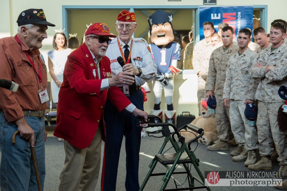 Departure ceremony emcee George Davidson, retired Marine Corps, passes the microphone to retired Navy aviator Mack MacLean, a WWII and Korean War veteran. The Patriots mascot is in the background.