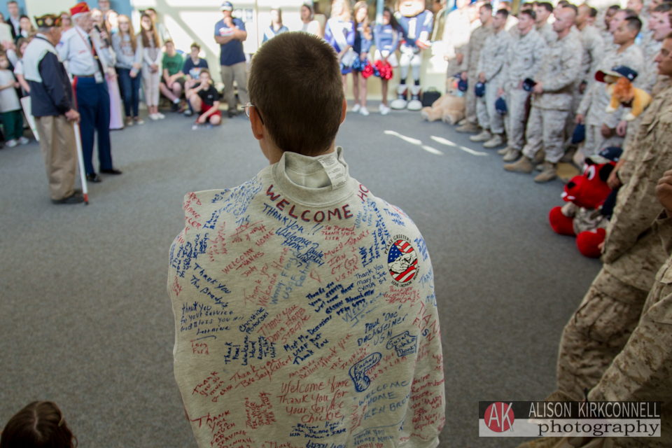 Windham High School student Travis Wallaker watches the ceremony as he waits to present the signed sweatshirt to the commander