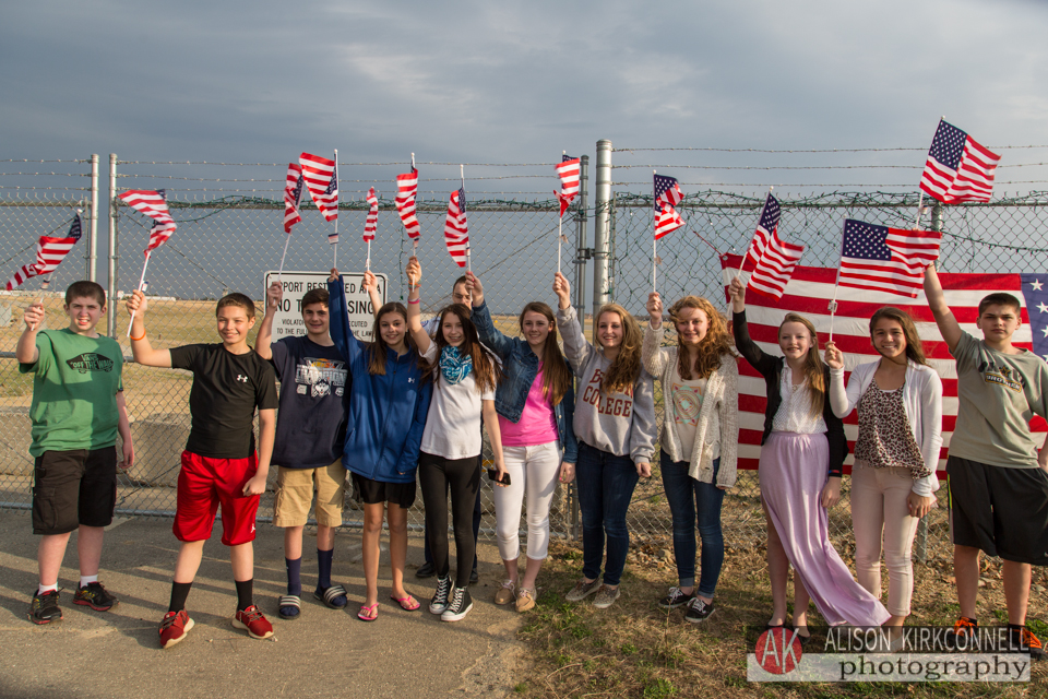 "The SMILES Club waits at the ""Fence Force"", where visitors wave flags at the charted aircraft carrying the soldiers as they depart"